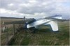 Figure 1: VH-MUV inverted after flipping over the airport perimeter fence. Source: Aircraft operator.