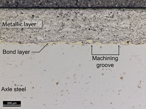 Metallurgical cross-section showing the applied surface layers and the steel substrate from the axle