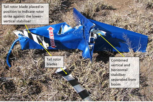 Figure 3: Combined horizontal and vertical stabilisers and tail rotor blades after their separation from the helicopter. One of the two tail rotor blades has been placed against the lower-vertical stabilizer to demonstrate the impact point after the initial strike with the dead and defoliated tree