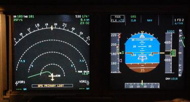 Figure 3: Photograph of an exemplar ND and the primary flight display during a simulated recreation of the flight scenario. Note the GPS PRIMARY LOST message (in yellow) at the bottom-left of the photograph and the green tracking line emanating from the white aircraft depiction at the centre of that representation