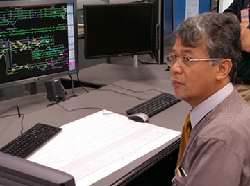 Suprapto Resorasmin (NTSC Head of Transport of Railway Accident Investigation Sub Committee) at the control panel in one of the training facilities at Queensland's Rail Management Centre, Brisbane.