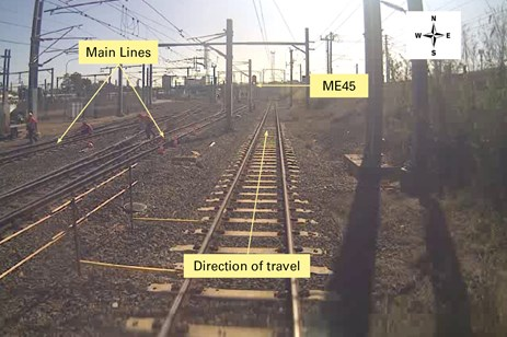 A still taken from CCTV footage from the driving compartment of train 1A21. Annotations show the main lines, the direction of travel, and the location of signal ME45.  It is likely that the driver's attention was diverted to the workers on the left of the photo and away from signal ME45. 