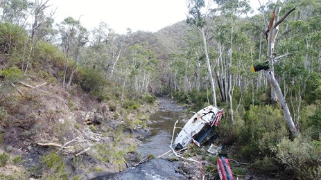 Figure 4: Helicopter wreckage in Yarrangobilly River. Wreckage of VH-HUE looking downstream away from the drill pad, in the approximate direction of flight.  Source: ATSB
