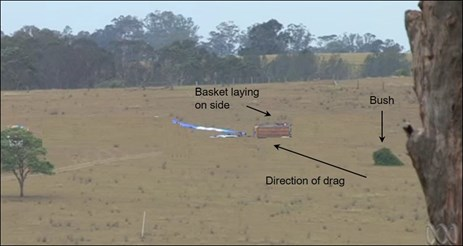 Figure 2: Landing site terrain with the deflated balloon, basket and the bush it contacted. Source: Australian Broadcasting Corporation with annotation by ATSB