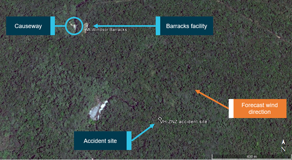 Figure 4: Accident site relative to barracks facility and causeway. Forecast wind direction indicating the accident site was located about 500–600 m upwind of the barracks facility and causeway.   Source: Google earth, annotated by ATSB
