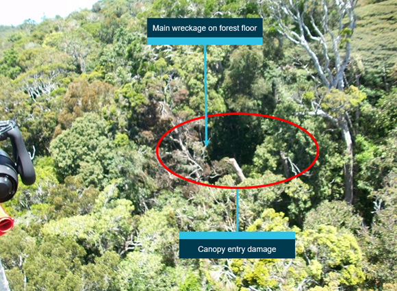 Figure 5: Approach to canopy entry directly above wreckage site. Rescue helicopter view of the damaged canopy. Main body of the helicopter is located on the forest floor, about 100 ft directly below the canopy damage.   Source: Search and rescue helicopter service (courtesy Queensland Police Service), annotated by ATSB