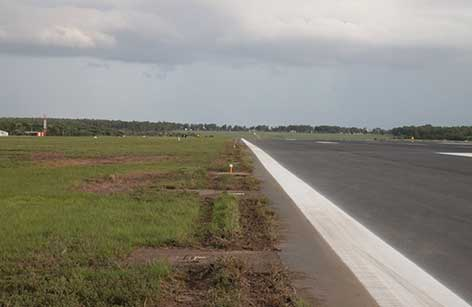 Image shows the tracks from the right main landing gear through grass and over concrete pads near the runway edge.