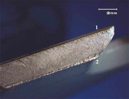 Figure 3: Fracture surface of section B, ratchet marks are visible at the serrated edge of the part (1) and the final fracture of the back edge of the part (2).