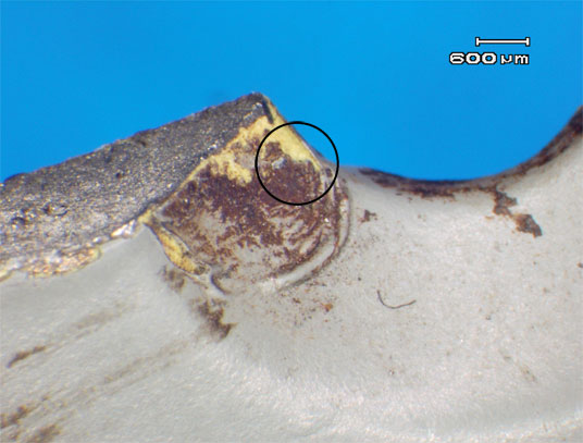 Figure 4: Oxide products within the elliptical holes of section B. Note the top coat deterioration and pleating (circled) revealing the chromate primer layer (yellow).