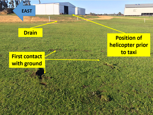 Figure 1: Marks where the helicopter tail and skid struck the ground. The drain the pilot planned to clear prior to transitioning to forward flight and hangar arein the background