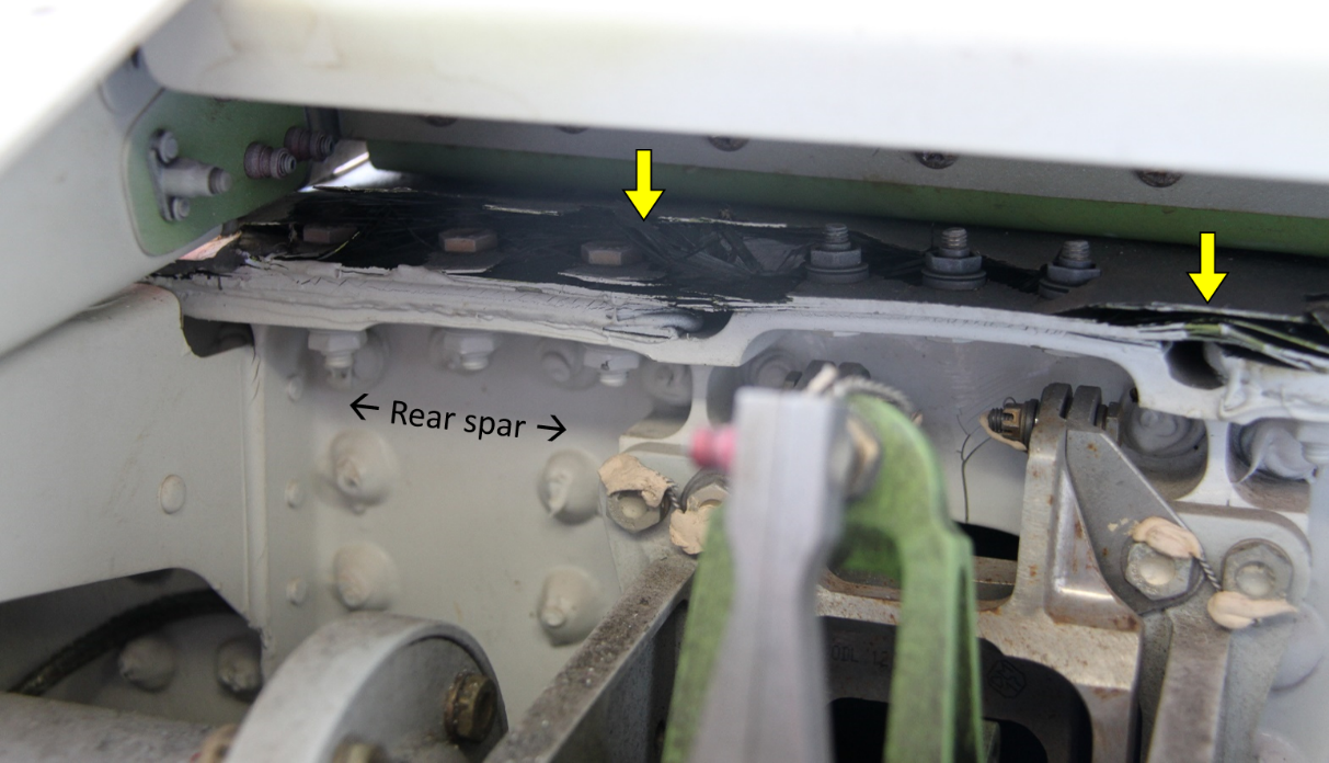 Figure 9: Cracking and delamination of the upper skin on the horizontal stabiliser at the rear spar. View looking forward at the rear face of the rear spar. Damage identified by yellow arrows