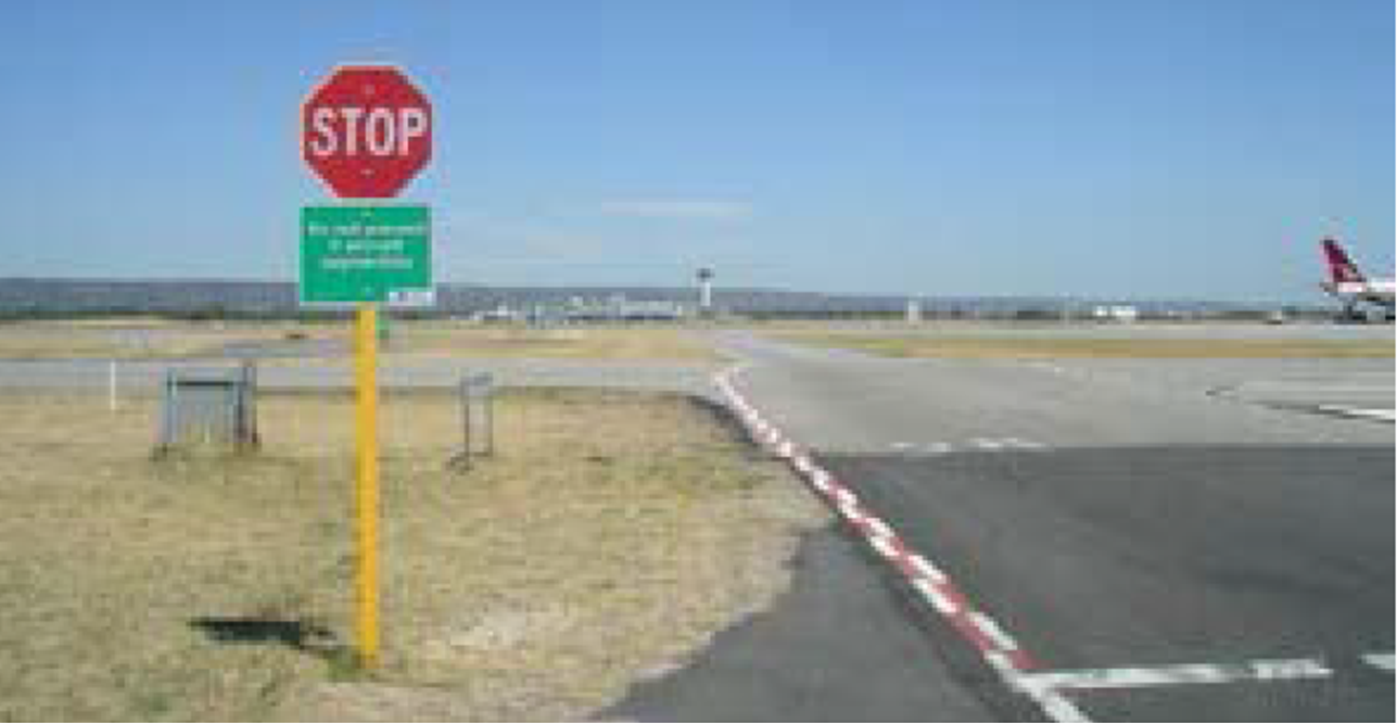 Figure 2: Photo showing stop sign and red and white zipper markings that denote a taxiway like that for taxiway R
