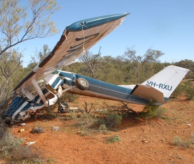 Photograph showing the accident site terrain and impact damage to the aircraft