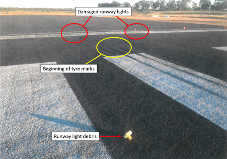 Figure 3: Runway 11 threshold. Image shows the damaged runway lights, touchdown tyre marks and runway light debris. Source: Airport operator, annotated by ATSB