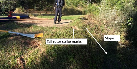 Figure 2: Sloping ground away from helipad and tail rotor strike marks. Source: Queensland Police