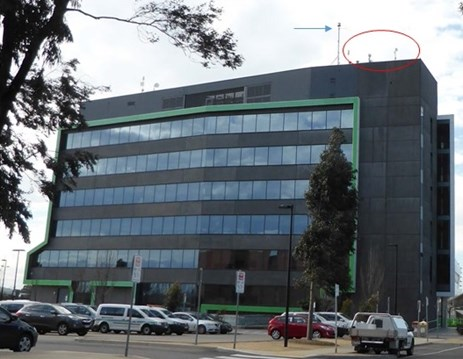 Figure 1: Hume City Council building showing the existing antennas (circled in red) and the (then) proposed radio mast (indicated with a blue arrow). Source: ATSB.