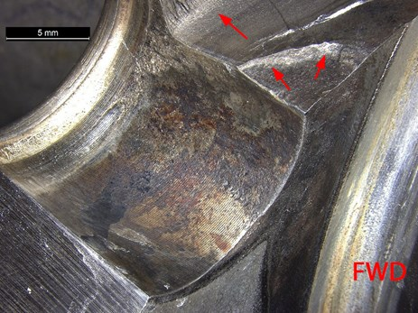 Figure 7: Corrosion observed within the bore of the dowel pin hole. Image show corrosion in bore, along with crack originating at the forward corner of the dowel pin hole (arrowed) Source: ATSB