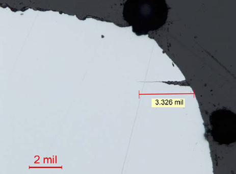 Figure 9: Metallographic cross section adjacent to the fracture surface showing secondary cracking. The micrograph shows the secondary cracking extending from the dowel pin hole in the region adjacent to the primary fracture surface. Also, note the corroded initial fracture surface at the top of the image, and the rounded fracture edge. Note that 2 mil is approximately equal to 50 µm. The crack length in the image is approximately 84 µm in length. Source: GE