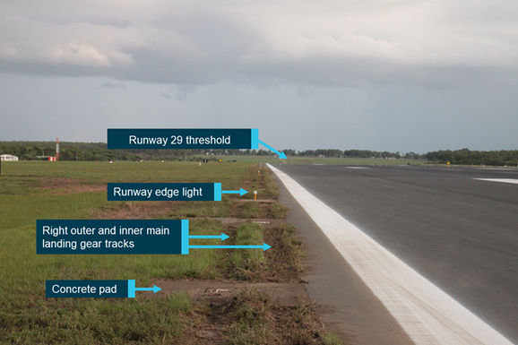 Figure 2: Wheel tracks where VH-VUI departed the runway 29 sealed surface and destroyed runway edge lights. Image shows the tracks from the right main landing gear through grass and over concrete pads near the runway edge. Photo facing the opposite direction to the landing. Source: ATSB