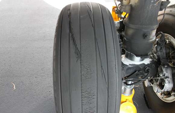 Figure 3: VH-VUI tyre damage. Image shows cut damage to the right main landing gear outboard tyre. The chevrons in the centre of the tread are normal. Source: ATSB