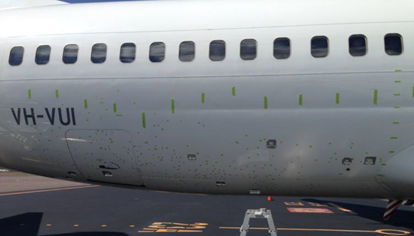Figure 4: VH-VUI fuselage damage, marked with green tape. Image shows the locations of skin damage to the right side of the aircraft fuselage marked with short sections of tape on the underside of the fuselage. Longer sections of tape mark the locations of longitudinal and vertical fuselage reference lines. Source: Virgin Australia