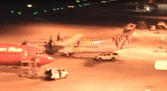 Figure 3: Aircraft visual inspection underway at 2306:44 with LAME 2 on the stand at the rear of the left wing. The circle and arrow indicate the location of the LAME and the direction of torchlight (still image copied from closed circuit TV footage)