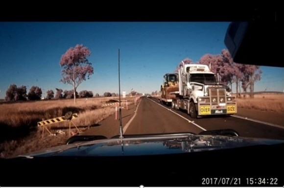 Figure 10: Dash camera footage from a private vehicle. The image shows a prime mover and low-loader carrying a front-end loader as it approached level crossing ID 2309. The time stamped on the image is 1534:22 on Friday 21 July 2017. Source: private vehicle operator