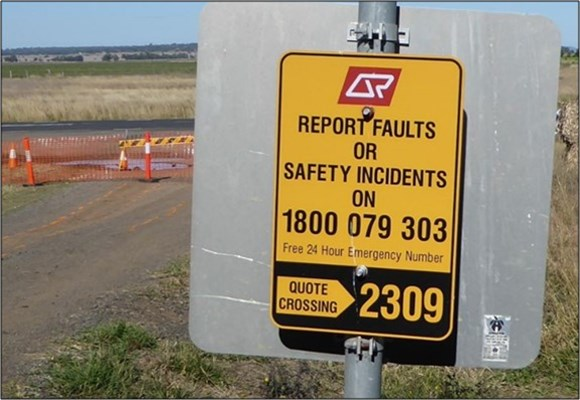 Figure 11: Incident reporting sign at level crossing ID 2309. The image shows the incident reporting sign and the emergency contact number, in place at level crossing ID 2309 on the day of the derailment. 